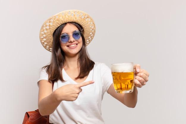 Junge reisende frau, die ein bier zeigt oder zeigt und hält