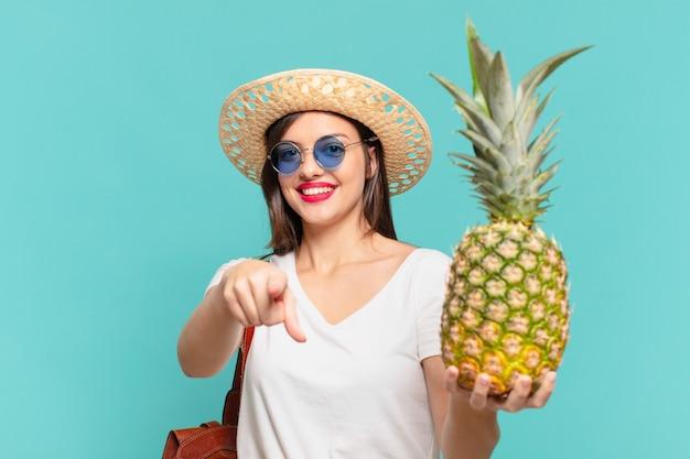 Junge reisende frau, die eine ananas zeigt oder zeigt und hält