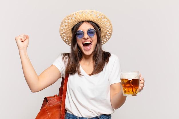 Junge reisende frau, die erfolgreich einen sieg feiert und ein bier hält