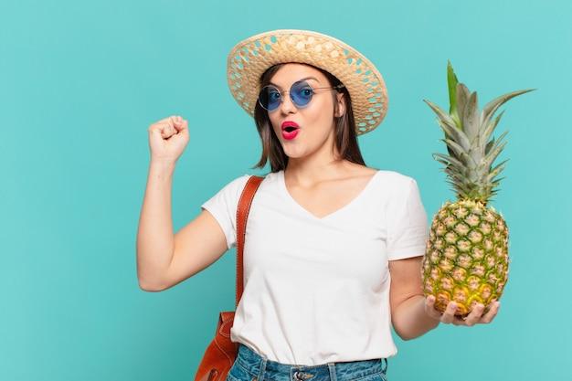 Junge reisende frau, die erfolgreich einen sieg feiert und eine ananas hält