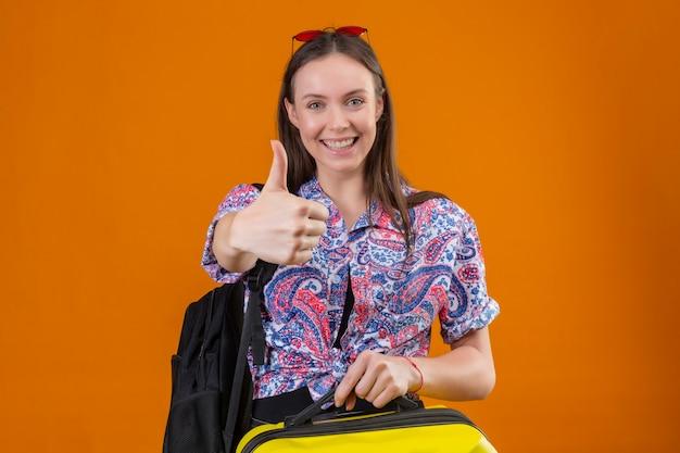 Junge reisende frau, die rote sonnenbrille auf kopf mit koffer hält, der rucksack hält, der kamera betrachtet, die fröhlich zeigt daumen oben über orange hintergrund stehend
