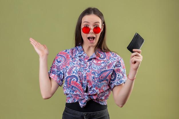 Junge reisende frau, die rote sonnenbrille hält, die brieftasche hält, die erstaunt und überrascht mit armen über grüner wand schaut