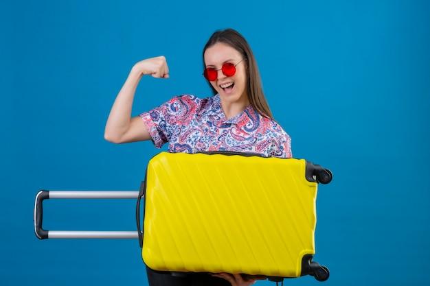 Junge reisende frau, die rote sonnenbrille hält, die gelben koffer hält, der glückliches und positiv lächelndes freudiges erhöhen der faust zeigt, die bizepssiegerkonzept über blauem hintergrund zeigt