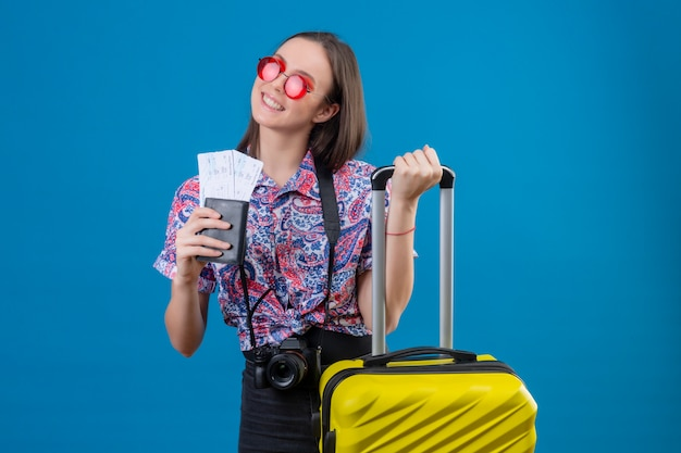 Junge reisende frau, die rote sonnenbrille mit gelbem koffer hält, der pass und tickets hält, die fröhlich mit glücklichem gesicht über blauer wand lächeln