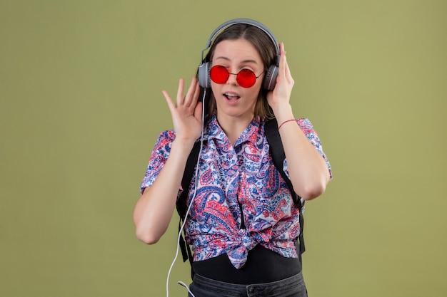 Junge reisende frau, die rote sonnenbrille trägt und mit rucksack musik hört, die kopfhörer mit glücklichem gesicht über grüner wand verwendet