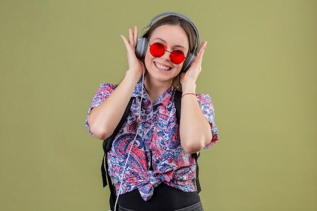 Junge reisende frau, die rote sonnenbrille trägt und mit rucksack musik hört, die kopfhörer verwendet, die mit glücklichem gesicht lächeln, das über grünem hintergrund steht