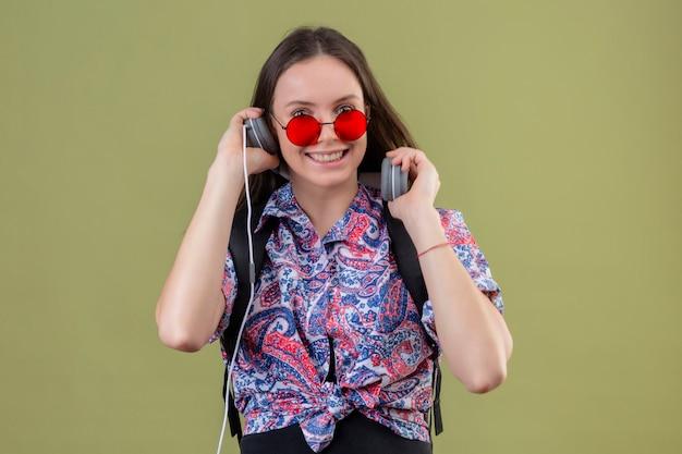 Junge reisende frau, die rote sonnenbrille trägt und mit rucksack musik hört, die kopfhörer verwendet, die mit glücklichem gesicht über grüner wand lächeln