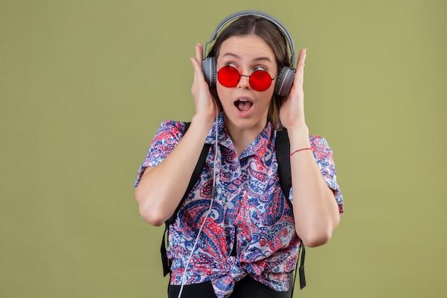Junge reisende frau, die rote sonnenbrille trägt und mit rucksack musik hört, die kopfhörer verwendet, die über grüner wand überrascht schauen
