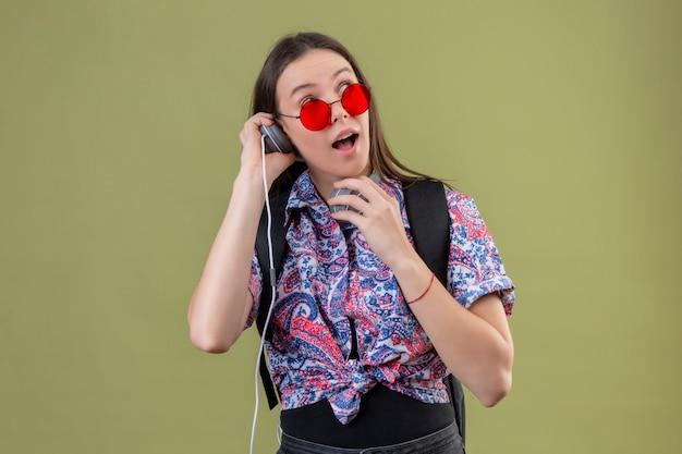 Junge reisende frau, die rote sonnenbrille trägt und mit rucksack musik hört, die kopfhörer verwendet, die über grüner wand überrascht und glücklich schauen