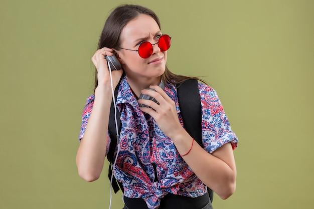 Junge reisende frau, die rote sonnenbrille und mit rucksack musik hört unter verwendung von kopfhörern unzufrieden mit stirnrunzelndem gesicht über grüner wand