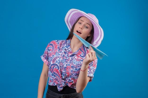 Junge reisende frau im sommerhut, der papierflugzeug spielerisch und glücklich steht über blauem hintergrund hält