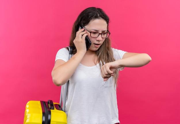Junge reisende frau im weißen t-shirt, das reisekoffer hält, der ihre hand betrachtet, die sich an zeit erinnert, während auf handy spricht, das über rosa wand steht