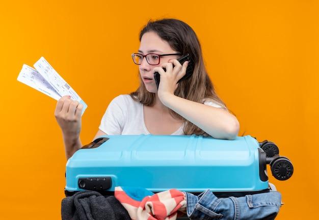 Junge reisende frau im weißen t-shirt stehend mit koffer voll von kleidern, die flugtickets betrachten, die sie überrascht betrachten, während auf handy über orange wand sprechen