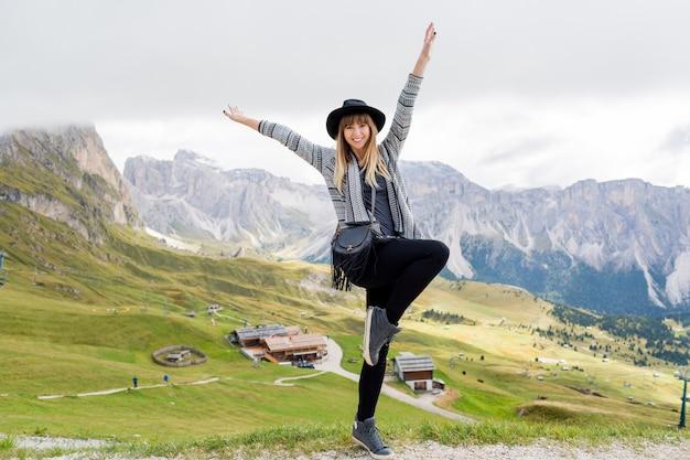 Junge reisende frau mit hut und rucksack, die erstaunlichen bergblick genießen