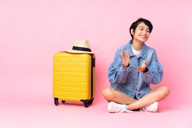 Junge reisende frau mit koffer, der auf dem boden über isoliertem rosa applaudierend nach präsentation in einer konferenz sitzt