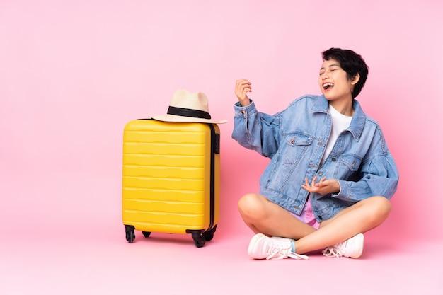 Junge reisende frau mit koffer, der auf dem boden über isoliertem rosa macht, das gitarrengeste macht