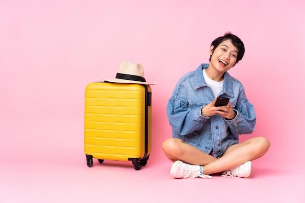 Junge reisende frau mit koffer, der auf dem boden über isoliertem rosa sitzt, überrascht und eine nachricht sendend