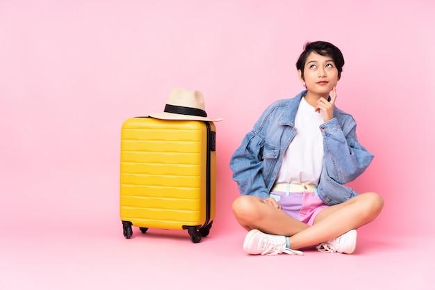 Junge reisende frau mit koffer, der auf dem boden über lokalisiertem rosa denken einer idee beim aufblicken sitzt