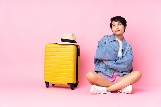 Junge reisende frau mit koffer, der auf dem boden über lokalisiertem rosa schaut, das beim lächeln aufblickt