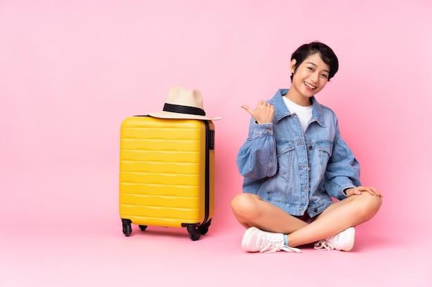 Junge reisende frau mit koffer, der auf dem boden über lokalisiertem rosa zeigt, das zur seite zeigt, um ein produkt zu präsentieren