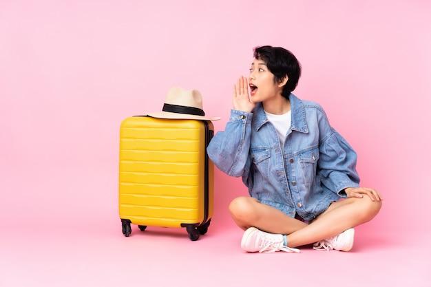 Junge reisende frau mit koffer, der auf dem boden über vereinzeltem rosa schreien mit weit offenem mund zur seite sitzt