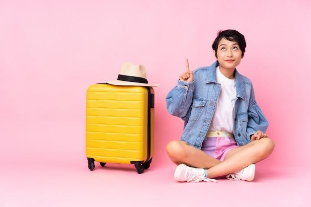 Junge reisende frau mit koffer sitzt auf dem boden über isoliertem rosa, das mit dem zeigefinger eine große idee zeigt