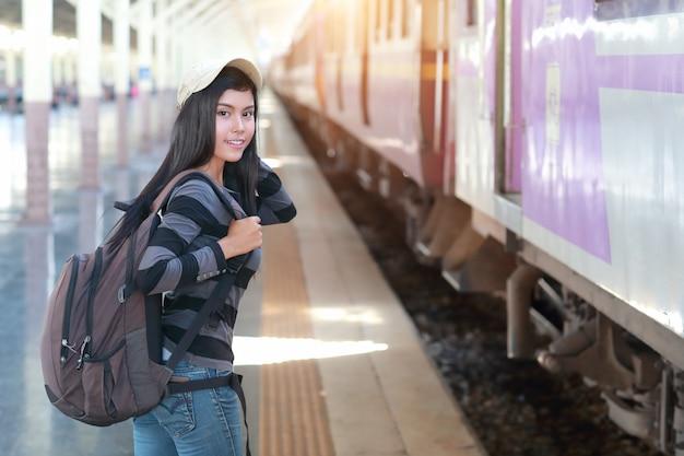 Junge reisende frau mit rucksack warten auf zug