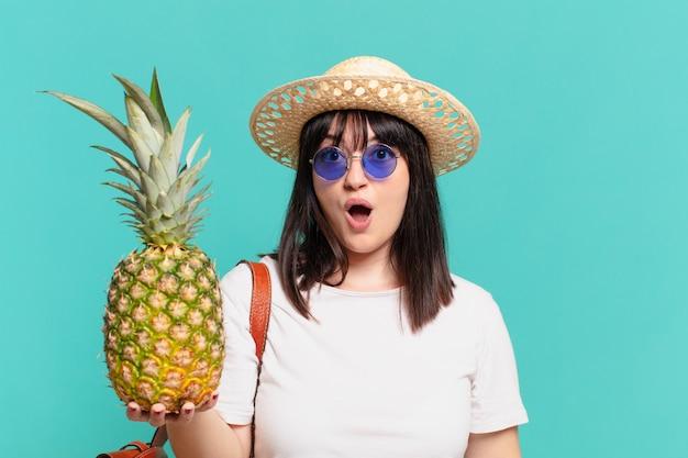 Junge reisende frau überraschte ausdruck und hielt eine ananas