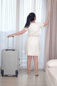 Junge reisende im weißen kleid mit ihrem gepäck kommt im hotelzimmer und offenem vorhang an, um eine außenansicht zu genießen, glücklicher frauenlebensstil mit urlaubskonzept