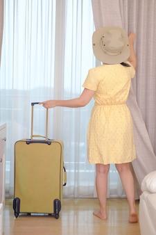 Junge reisende in gelbem kleid mit ihrem gepäck kommt im hotelzimmer und offenem vorhang an, um eine außenansicht zu genießen, glücklicher frauenlebensstil mit urlaubskonzept für sommerreisen