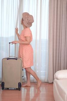 Junge reisende in rosa kleid mit ihrem gepäck kommt im hotelzimmer und offenem vorhang an, um eine außenansicht zu genießen, glücklicher frauenlebensstil mit urlaubskonzept für sommerreisen