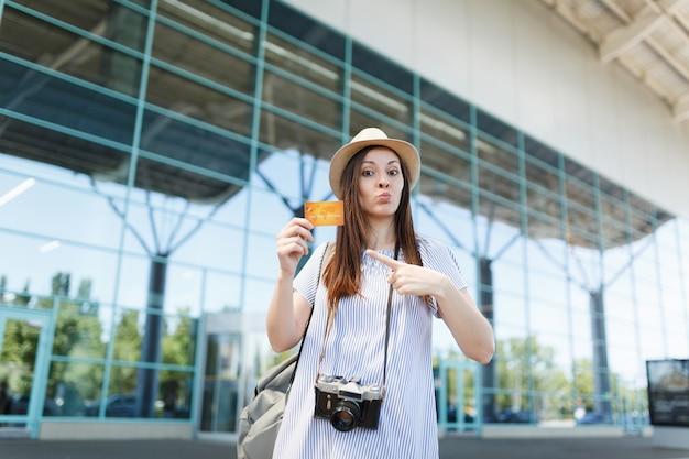 Junge reisende touristenfrau mit hut mit retro-vintage-fotokamera, zeigefinger auf kreditkarte am internationalen flughafen zeigend