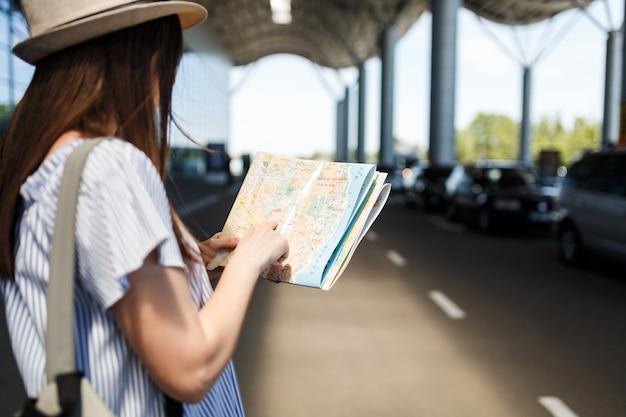 Junge reisende touristenfrau mit hut mit rucksack, die route in papierkarte am internationalen flughafen sucht