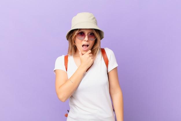 Junge reisende touristenfrau mit mund und augen weit offen und hand auf kinn