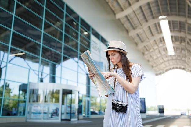Junge reisende touristenfrau mit retro-vintage-fotokamera-suchroute in papierkarte am internationalen flughafen