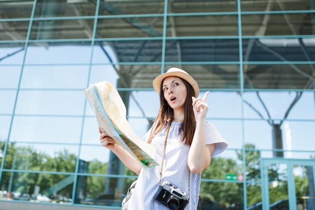 Junge reisende touristenfrau mit retro-vintage-fotokamera sucht route in papierkarte am internationalen flughafen?