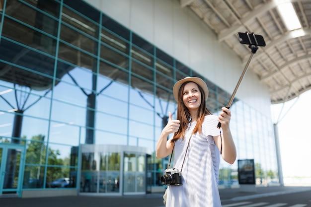 Junge reisende touristenfrau mit retro-vintage-fotokamera zeigt daumen hoch, die selfie auf dem handy mit egoistischem einbeinstativ am flughafen macht