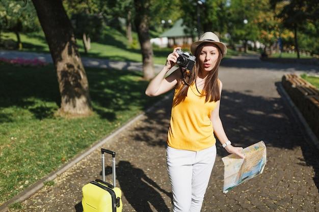Junge reisende touristische frau mit hut mit koffer, stadtplan fotografieren auf retro-vintage-fotokamera in der stadt im freien. mädchen, das ins ausland reist, um am wochenende zu reisen. tourismus reise lebensstil.
