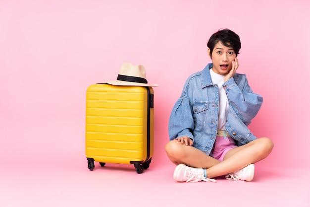 Junge reisende vietnamesische frau mit koffer, der auf dem boden über rosa wand mit überraschtem und schockiertem gesichtsausdruck sitzt