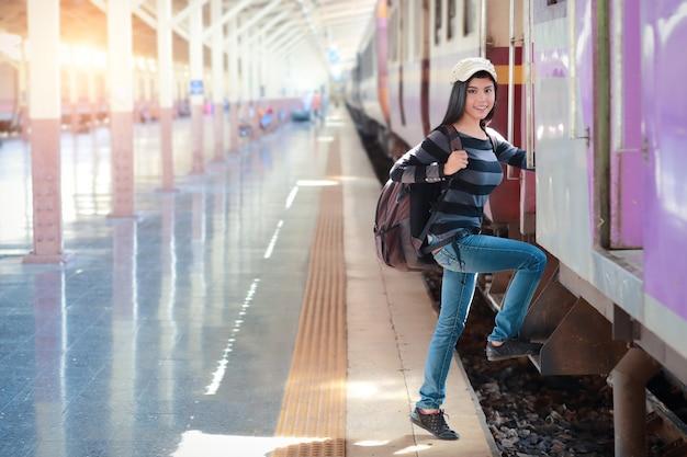 Junge reisendfrau mit dem rucksack, der in den zug einsteigt