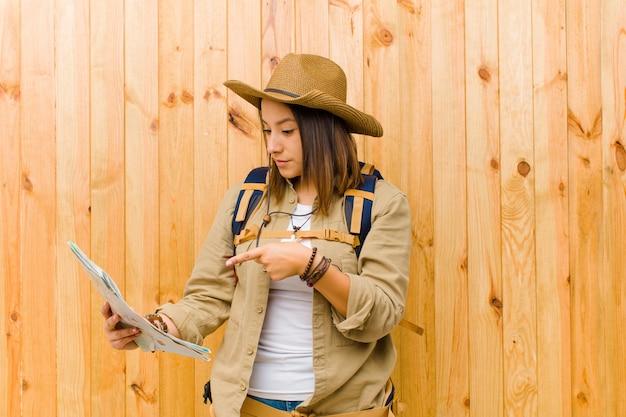 Junge reisendfrau mit einer karte gegen hölzerne wand