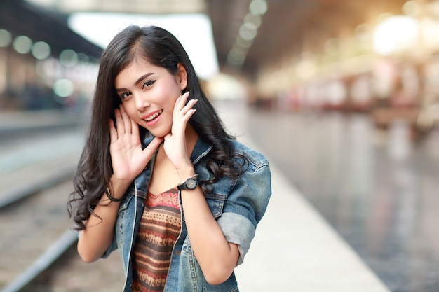 Junge reisendfrau mit jackenbaumwollstoffwartezug