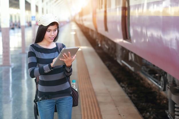Junge reisendfrau mit rucksack unter verwendung der tablette während des reisens am feiertag