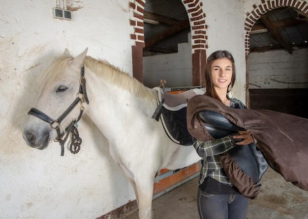 Junge reiterfrau mit schimmel