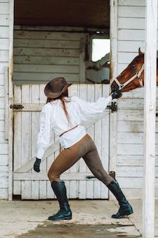 Junge reiterin, die ein weißes hemd und hut trägt, führt ihr pferd aus dem stall für einen spaziergang.