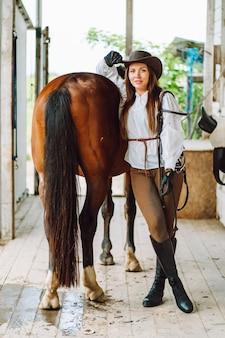 Junge reiterin trägt ein weißes hemd und hut mit ihrem braunen pferd in einem stall, porträt.