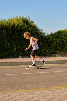 Junge reitet skateboard entlang der straße