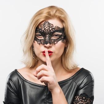 Junge reizend blonde dame in der maske mit dem finger nahe lippen