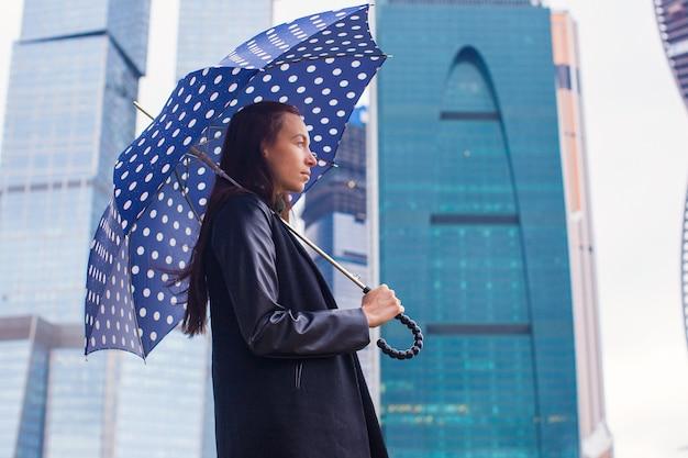 Junge reizend geschäftsfrauen, die unter einen regenschirm an einem regnerischen tag gehen