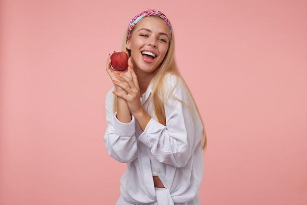Junge reizende blonde frau mit orange maniküre im weißen hemd, das pfirsich nahe wange sucht und hält, positiv und glücklich, isoliert